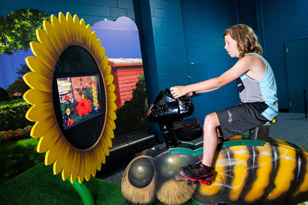 Boy on bee bike in Backyard Adventures exhibit. Photo by Imagine Exhibitions, Inc.