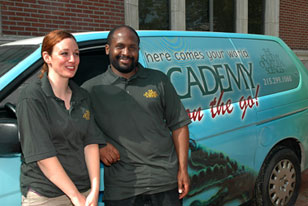 two academy educators next to the Academy-on-the-Go van