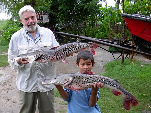 photo of scientist and boy holding large catfishes