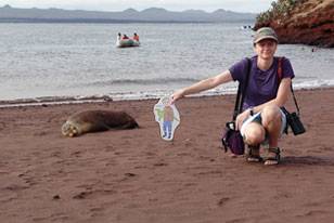 Joe on the Go and Academy educator pose next to a seal on the Galapagos