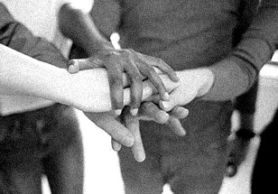 A close up image of kids putting their hands on top of one another.