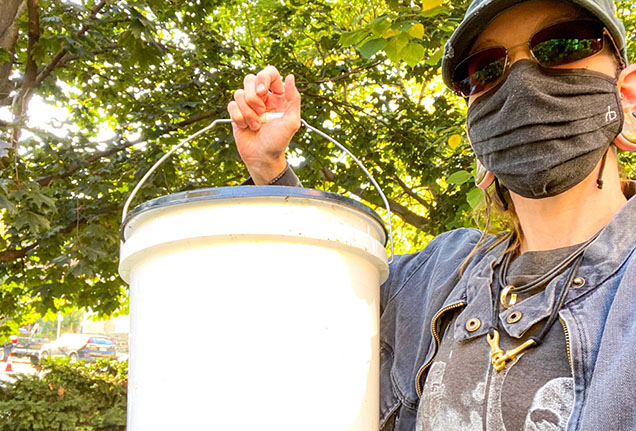 woman with sunglasses and covid mask holds compost bucket