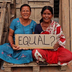 Two Indian women siting, holding a sign that says Equal?