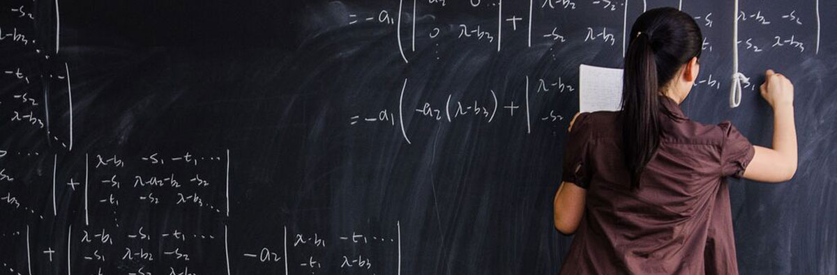 Student working through an equation on chalkboard