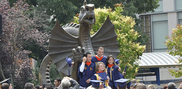 Photo of graduating students in front of Dragon Park Statue